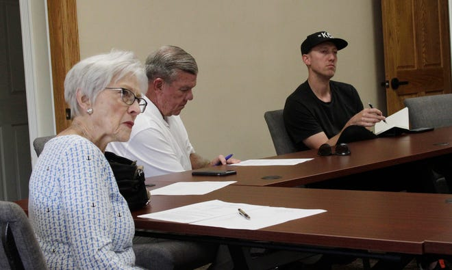 Moberly Historic Preservation Committee members Sara Fleming, left, and Adam Flock, right, listen to a presentation made while Doug Sharp takes notes during a July 13 public business meeting held at the Municipal Building in downtown Moberly.