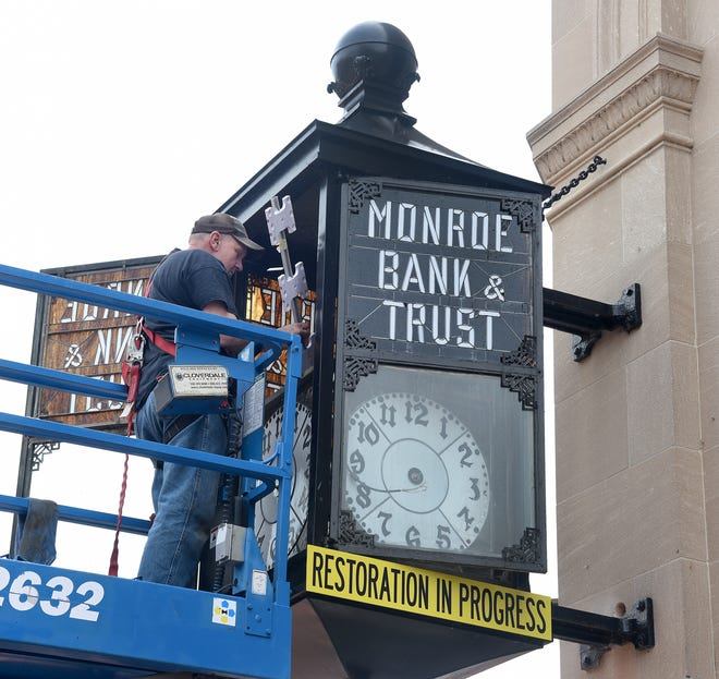 Larry Dillon restores the old clock attached to a First Merchants building in downtown Monroe. The clock will now chime and make sound on the hour, each hour.