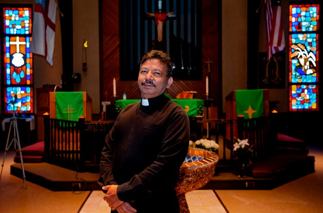 "The Rev. Natividad ""Naty"" Menjivar poses for a photo in the sanctuary of Santa Maria Virgen Episcopal Church, where he serves as vicar."
