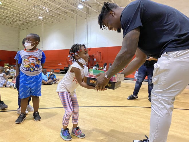 Dolphins linebacker Jerome Baker hands a gift box to Rochelle White, 5, during Wednesday's 'Christmas in July' event.