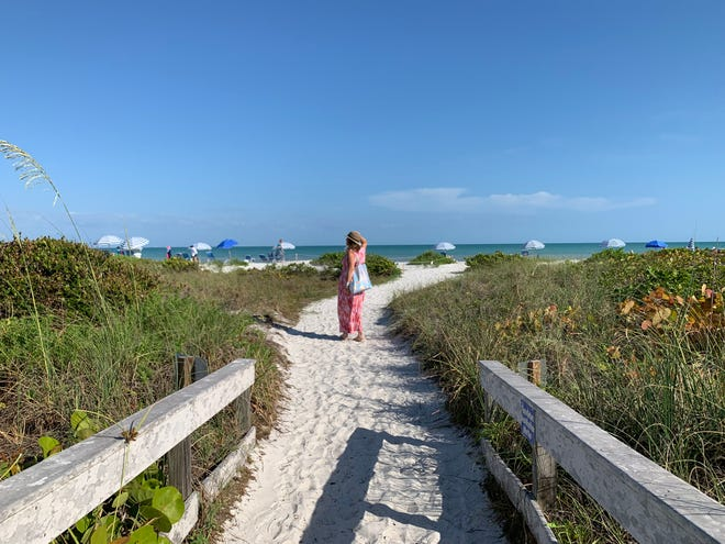 Charlene Peters takes the the path to the beach from Sanibel Moorings on Sanibel Island.