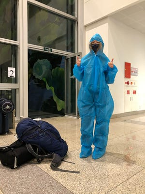 Madeleine List wears a hazmat suit upon her arrival in Vietnam before being sprayed with disinfectant and tested for COVID.