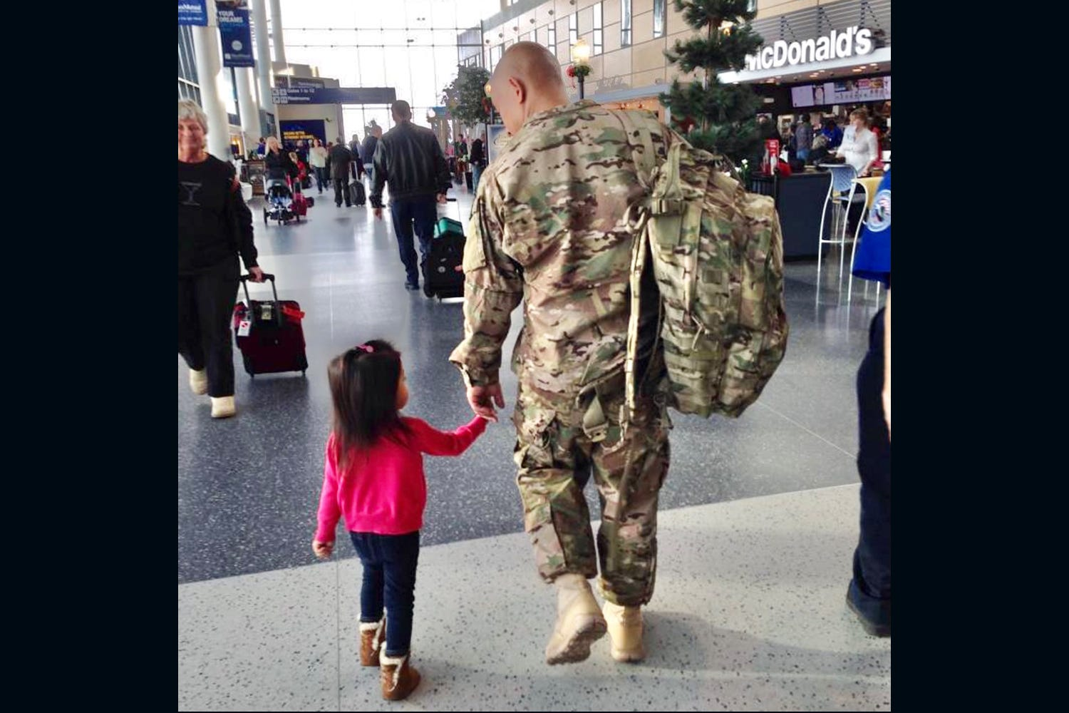 Nhem with his daughter Madison, age 2 at the time, at Bradley Airport in Hartford, Conn., on his way to his second deployment to Afghanistan in December 2013, this time as an Air Force officer.