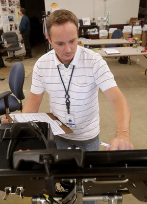 """Stark County Board of Elections warehouse manager Aaron Casto runs an """"acceptance test"""" on a new Dominion ImageCast X voting machine. The new machines began arriving at the elections board earlier this month."""