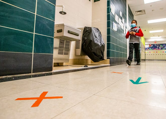 Third-grade student Damarcus Conroy walks by a specially converted water fountain and tape on the floor that directs foot traffic inside the halls at Madison Steam Academy, due to COVID-19 safety protocols, on April 30 in South Bend. Local health officials are worried about the delta variant of the virus as schools get ready to resume in the coming weeks.