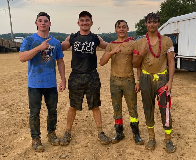 """Four Owen Valley High School wrestlers joined forces to compete as """"Squeeze 'em Till They Squeal,"""" in they annual hog wrestling competition at the Owen County Fair. From left, Logan Cain, Charlie Campbell, Branson Weaver and Quaid Hinshaw battled the slippery swine to grab the lowest time of the 2021 event, 4.65 seconds, More photos from this year's hog wrestling event are featured in today's SEW."""