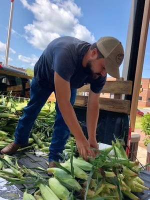 Joe Costner, of Costner Farms in Fallston, stacks corn for sale at the Wednesday Farmers Market on West Marion Street.