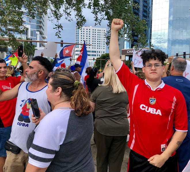 Sarasota resident Jorge Montoya, right, participated in a demonstration Tuesday in downtown Sarasota in solidarity with anti-government protesters in Cuba. Montoya was born in Cuba
