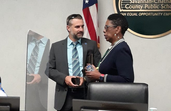 David Bringman, District 6 board representative, talks with District Superintendent Ann Levett after Wednesday's board meeting.