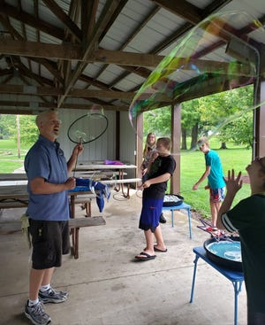 Ken Cooper, left, with Absolute Science, of Davenport, Iowa, delighted camper Megan Painter, right, with his bubble making skills at the Kewanee Park District Special Needs Camp on Monday. The camp is supported by the Kewanee Park District, the Kewanee Elks and Abilities Plus, which provided a grant to the camp to pay for the bubble station.