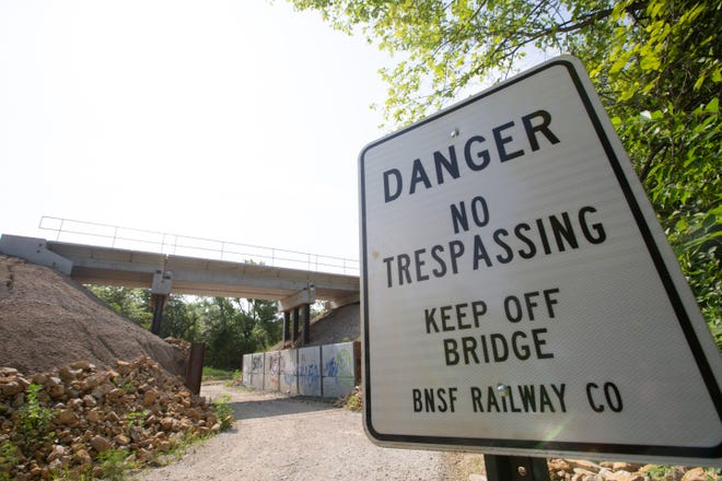 No trespassing signs are placed near a BNSF Railway bridge that runs over the Landon Trail just east of S. Kansas Avenue and 33rd Street. The trail remains unpaved following the construction of the bridge, but officials with BNSF say they are working to pave the area soon.