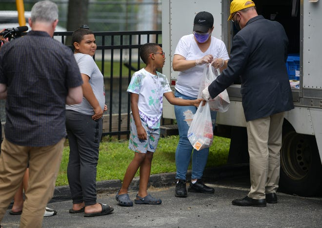U.S. Rep. James P. McGovern hands out food along with Nannette Corchado, a nutrition helper during one of three stops, this one at Washington Heights Wednesday. The congressman and representatives from Project Bread were highlighting the ongoing impact of the pandemic on childhood hunger.