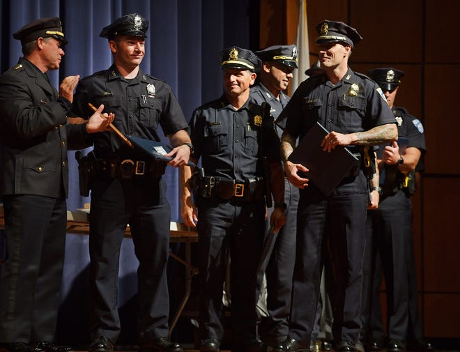 At left, Chief Steve Sargent applauds along with family and friends as Officer Robert D. Sansoucy is awarded the Valor Award; he is pictured with fellow officers also recognized for their bravery in saving a suicidal man who was threatening to jump from the Union Station garage. The Police Department held an award ceremony to recognize several police officers for acts of bravery and heroism at Worcester Technical High School on Wednesday.
