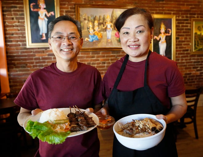 Bo and Leanna Prum hold two of their signature dishes at Prum's Kitchen, a restaurant in downtown Gainesville.