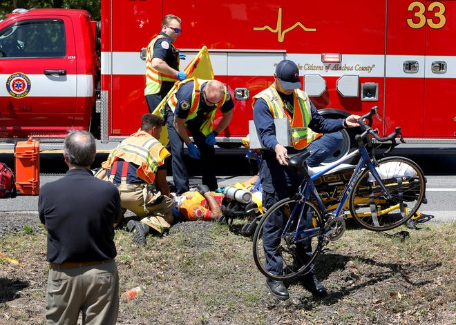 First responders with Gainesville Fire Rescue and Alachua County Fire Rescue work to help a bicyclist that was hit by a car in Gainesville.