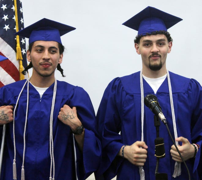 After graduating magna cum laude with associates degrees from Trinidad State College, Youthful Offender System inmates  Ruben Martinez (left) and Demitrius Herron pose for a picture.