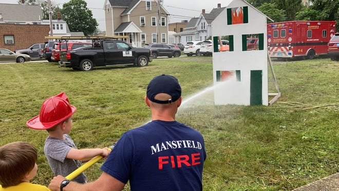 Cole Salvato douses some flames with help from firefighter Joe Ezersky at Family Fun Night July 13 in downtown Mansfield.
