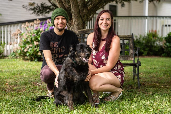 Nate Burner (left), Jessica Lovegrove, and their dog, Ari, pose for a photo in front of their rental home in West Asheville on Wednesday, July 14, 2021. The couple opted to stay in the rental market for now after trying for several months to find a home to buy.