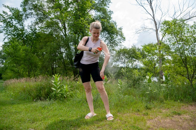 Lauren Bradford from Battle Creek reapplies bug repellant after leaving the beach at Fort Custer Recreation Area on Wednesday, July, 14, 2021 in Augusta, Michigan.