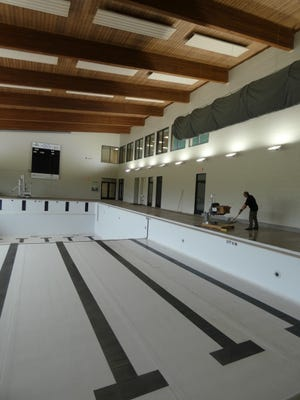 Brian Riffle, branch manager of the Bucyrus Area YMCA, scrubs the new flooring surrounding the facility's pool on Tuesday. The pool is expected to be filled this week.