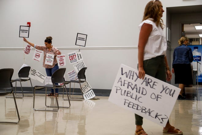 Karen Walker, left, sorts out a strung up display of signs with slogans and issues the group brought to a school board meeting at the Clarksville-Montgomery County School System main offices in Clarksville, Tenn., on Tuesday, July 13, 2021.