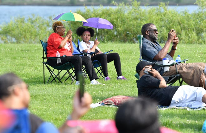 From left, Pamela Smith, 64, of Detroit sits with her granddaughter London Smith, 11, during a tribute concert honoring frontline workers during the COVID-19 pandemic at Belle Isle in Detroit on July 14, 2021.