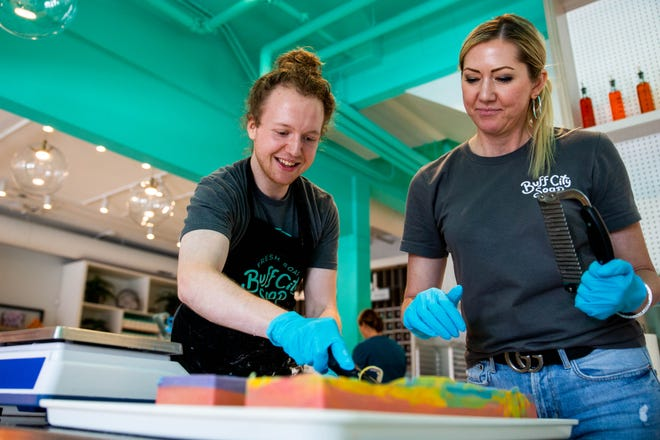 From left, Buff City Soap soap maker J Samways and COO Michelle Bogue cut freshly made soap into bars Tuesday, July 13, 2021 at the new store in downtown Brighton.
