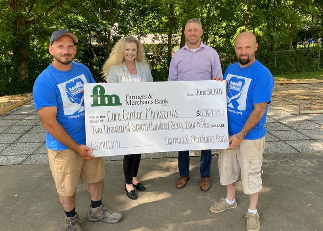 Pictured, from left, are Charles Lott with Care Center Ministries, Farmers and Merchants Bank Marketing and Community Relations Administrator Amber Henry, Market President Brandon Scallion and Jacob Lansdale with Care Center Ministries.