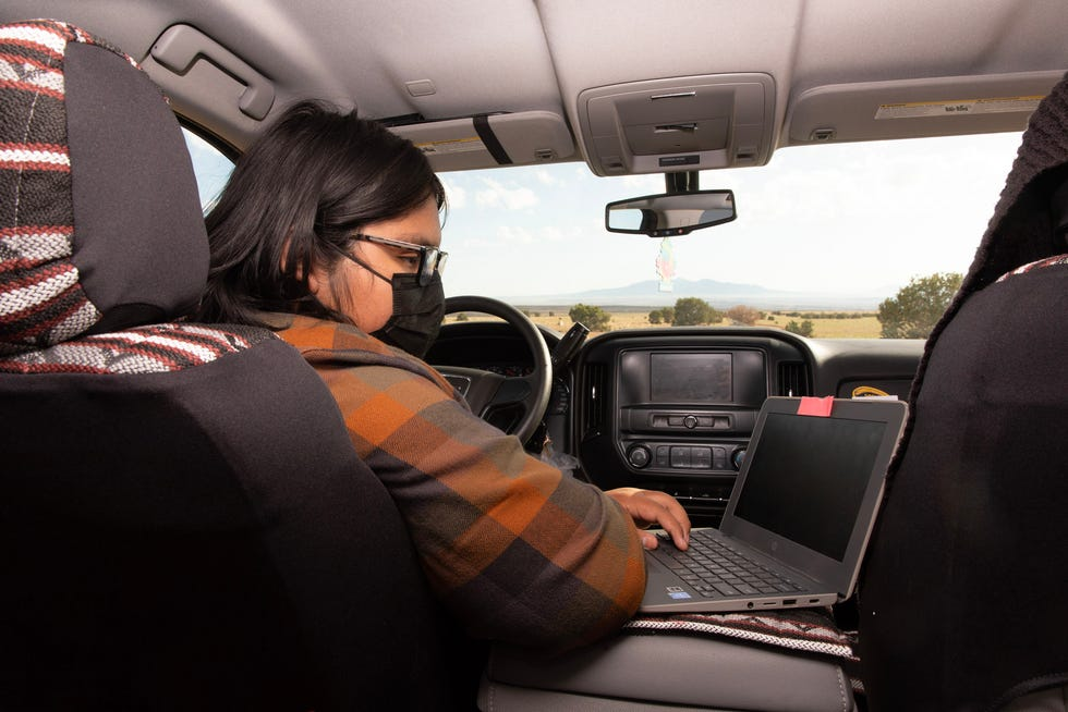 High school student Evan Allen attends virtual classes from his grandmother's truck on the Navajo Nation, surrounded by high desert.