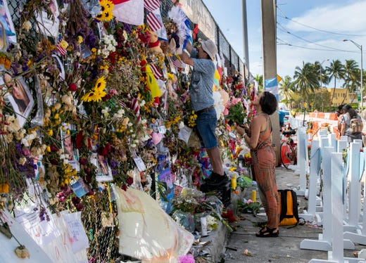 A couple adds fresh flowers to the memorial wall at the site of the Champlain Towers South collapse on Wednesday, July 14, 2021, in Surfside.