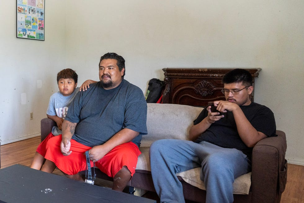 Clifton Mariano, middle, and two of his 10 children watch television at their home in Shiprock, New Mexico.