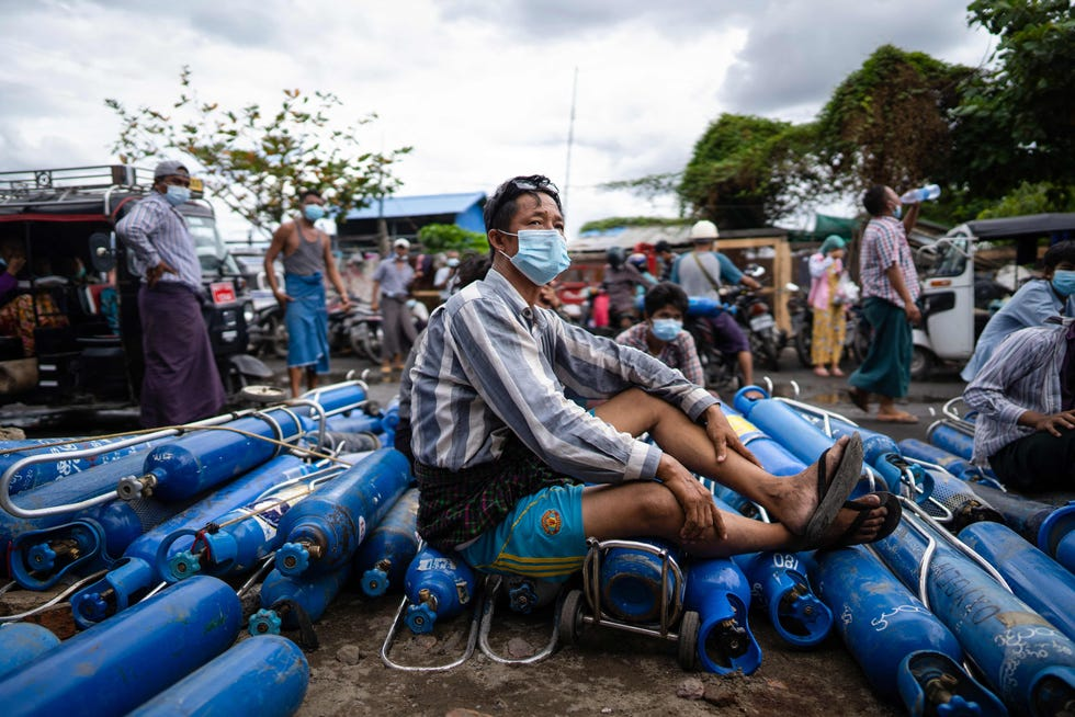 July 13, 2021:  A man sits on empty oxygen canisters, as he waits to fill them up, outside a factory in Mandalay amid a surge in Covid-19 coronavirus cases.