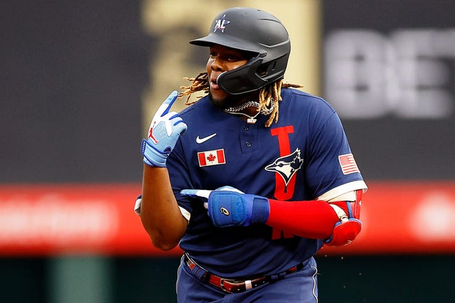 Vladimir Guerrero Jr. points to his bicep as he rounds the bases after his home run.