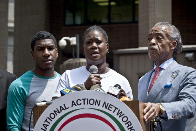 Trayvon Martin's mother, Sybrina Fulton, flanked by Trayvon's brother, Jahvaris Fulton, and the Rev. Al Sharpton, speaks during a rally organized by the National Action Network in New York on July 20, 2013.