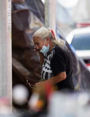 A woman visits the memorial wall at the site of the Champlain Towers South collapse on Wednesday, July 14, 2021, in Surfside.