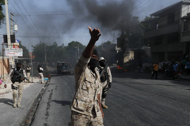Police clear burning tire road blocks set by protesters upset with growing violence in the Lalue neighborhood of Port-au-Prince, Haiti, Wednesday. Haitian President Jovenel Moise was assassinated on July 7. [AP PHOTO/FERNANDO LLANO]