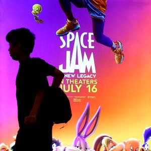 """A young moviegoer passes a poster for """"Space Jam: A New Legacy"""" on Thursday in Akron."""