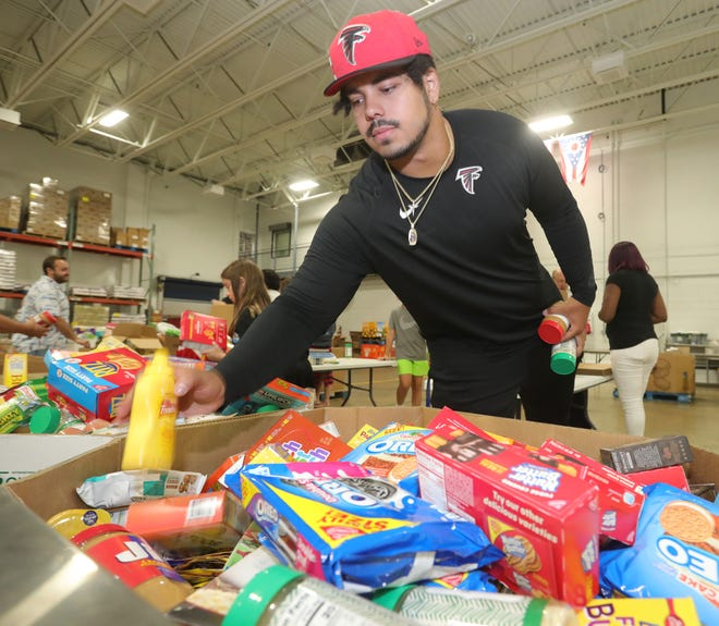 Atlanta Falcon offensive lineman and Coventry High School graduate Bryce Hargrove selects food items for packaging while volunteering Thursday at the Akron-Canton Regional Foodbank.