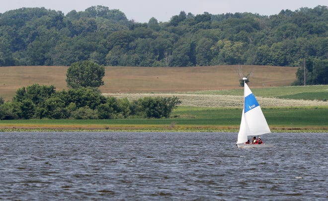 A sailboat is seen from the village of Chippewa Lake beach park as it sails past farmland.