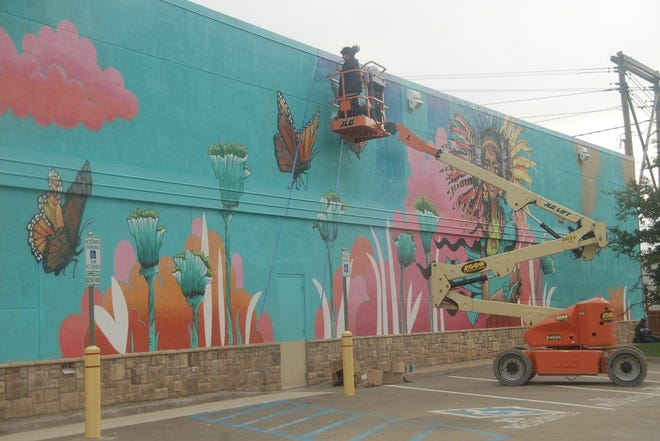 An artist crafts a mural on a downtown building located at 406 S. Polk St. during the inaugural Hoodoo Mural Festival in 2019. Officials released information on the 2021 iteration of the festival Thursday.