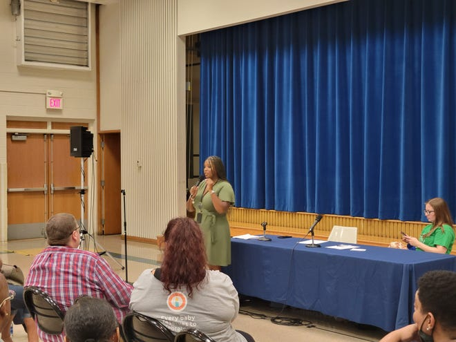 Assistant City Attorney Tiara Ross speaks to Colonial Village residents Wednesday night during a public forum about legal action the city is taking to compel the owner and property manager at the East Side apartment complex to address serious problems with living conditions.