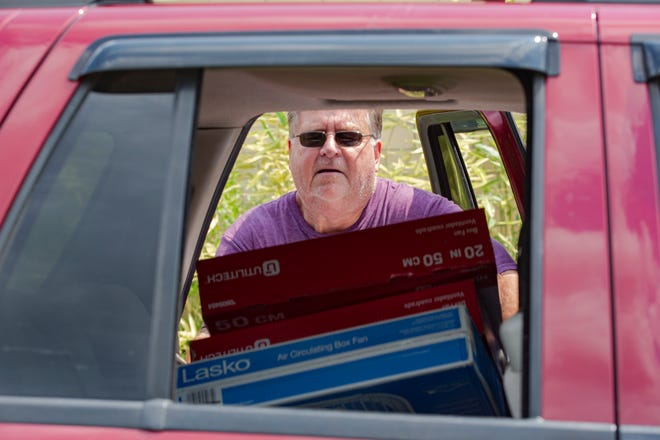 Dan Murnane, of Grove City, loads fans into the back of a car Wednesday at LifeCare Alliance's distribution center on Harmon Avenue as part of a fan giveaway to help cool off citizens during the summer.