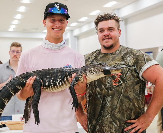 Mason Drube, a high school football player from Wyoming attending this weekend's Manning Passing Academy in Thibodaux,  poses Thursday with ZZ Loupe of Zam's Swamp Tour in Kraemer and one of his alligators. It was the first time Drube had held one.