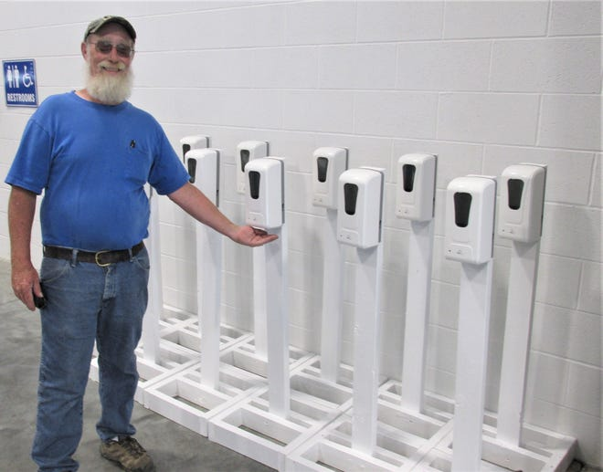 Fairgrounds manager Tim Hershberger displays the touchless hand sanitizers that will be available around the fairgrounds.