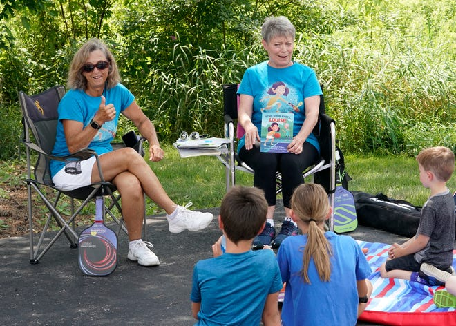 """Authors Karen Worthy of Jackson, left, and Jackie Freeman of Onsted explain the game of pickleball Wednesday during a program at the Lenawee District Library. Freeman and Worthy wrote """"Bend Your Knees, Louise!"""" to introduce kids to pickleball."""