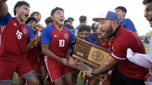 Dodge City High School soccer coach Saul Hernandez celebrates with his team after winning the state championship trophy.