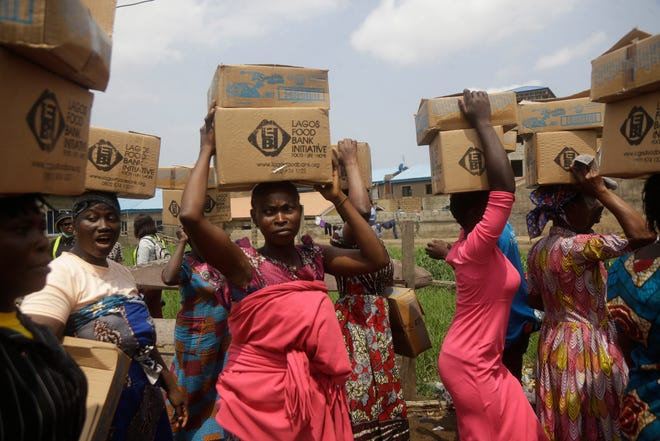 Residents of Oworonshoki Slum carry their food parcels distributed by the Lagos Food Bank Initiative, a non-profit nutrition focused initiative committed to fighting hunger and solving problems of Malnutrition for poor communities , in Lagos, Nigeria, Saturday, July 10, 2021.