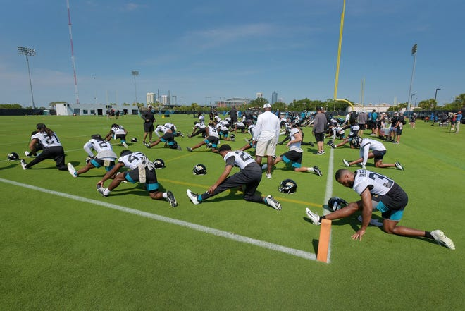 Players stretch on the practice field during Tuesday's minicamp session. The Jacksonville Jaguars held their Tuesday morning session of the team's mandatory minicamp at the practice fields outside TIAA Bank Field, June 15, 2021. [Bob Self/Florida Times-Union]