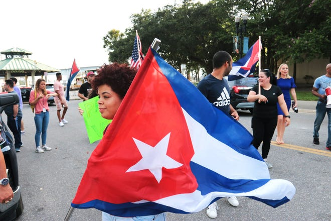 Melissa Neyra walks with the crowd displaying her flag Wednesday as protesters gathered at the former site of the Jacksonville Landing to advocate for Cuban freedom and for U.S. military intervention in the country.