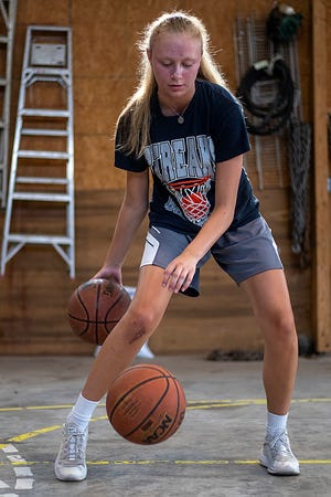 Recent Galesburg High School graduate Riley Jenkins dribbles inside a barn at the home of her former Junior Streaks coach, Steve Watts, in East Galesburg on Wednesday, July 14, 2021. She is on the mend from season-ending knee surgery.